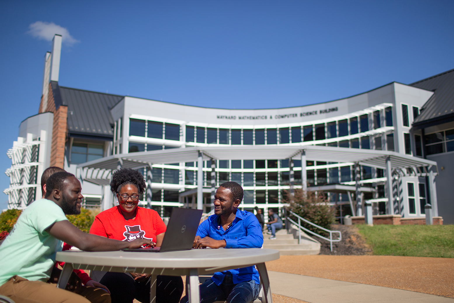 Students sit around a laptop looking at potential programs