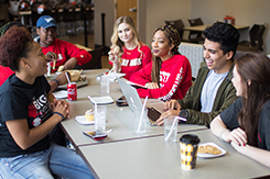 Students sit at table in cafeteria