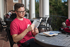 Student reads book on Harned balcony