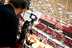 Student operates camera at basketball game